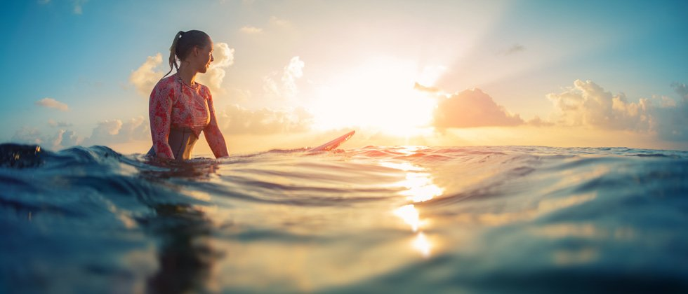 A woman surfer sitting on her board in the middle of the ocean