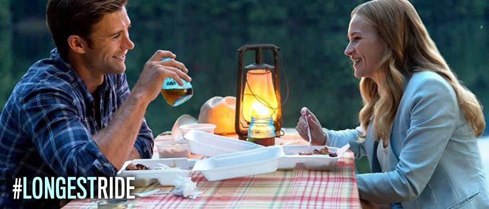A couple having a picnic in the middle of the woods by candlelight