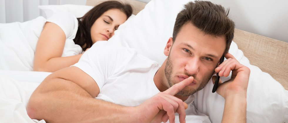 A couple sitting in bed - one sleeping the other one is secretly the phone