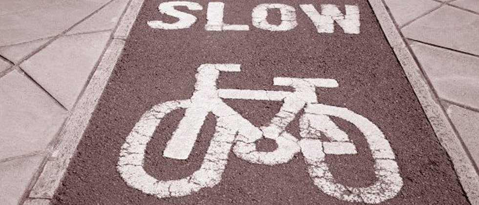 A picture of a bike lane with SLOW written across it