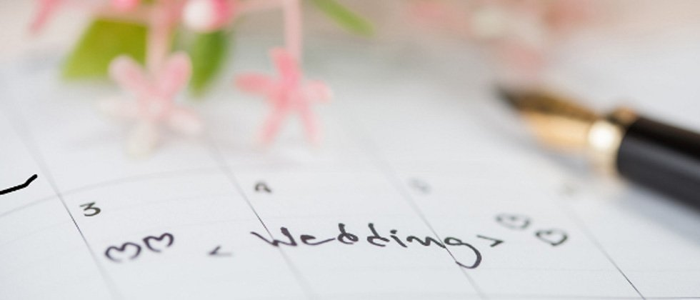 A calendar showing a date that has wedding written with hearts around it