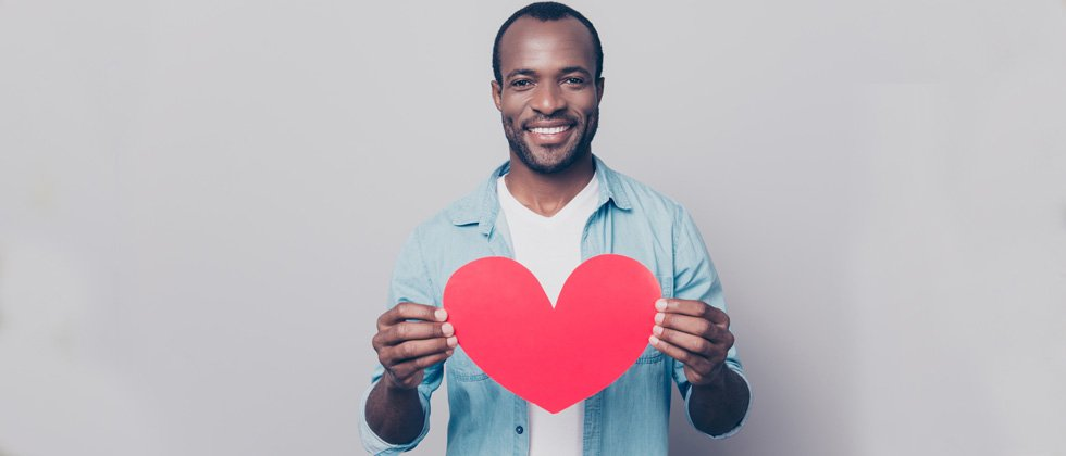 A man standing holding up a cutout heart & smiling