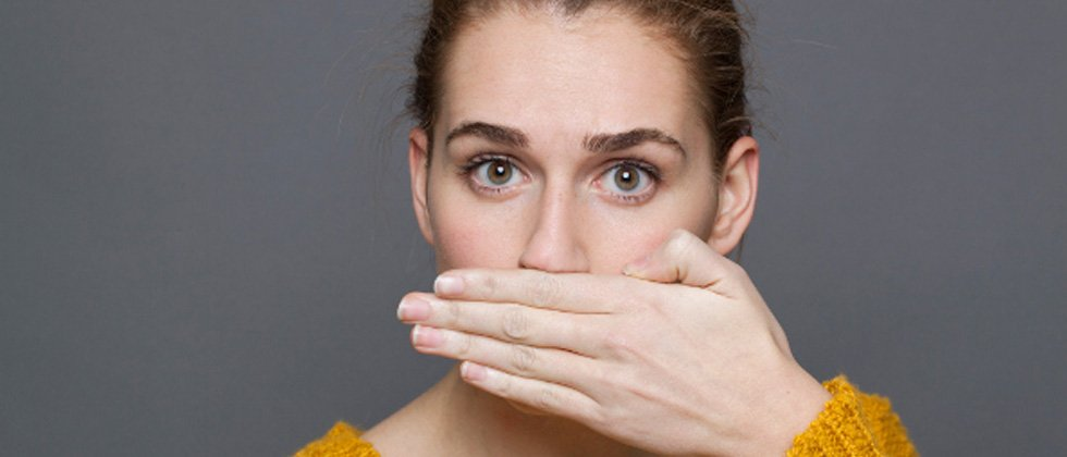Woman staring into the camera with her hand covering her mouth