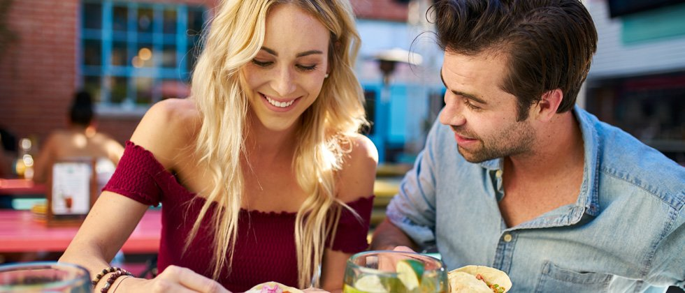 Couple smiling and eating on a lunch date