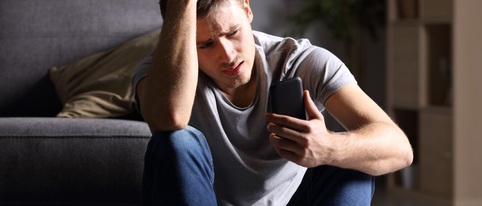 Worried and upset man sitting on the ground looking at his phone