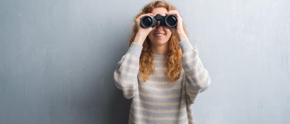 A woman looking into the camera through binoculars