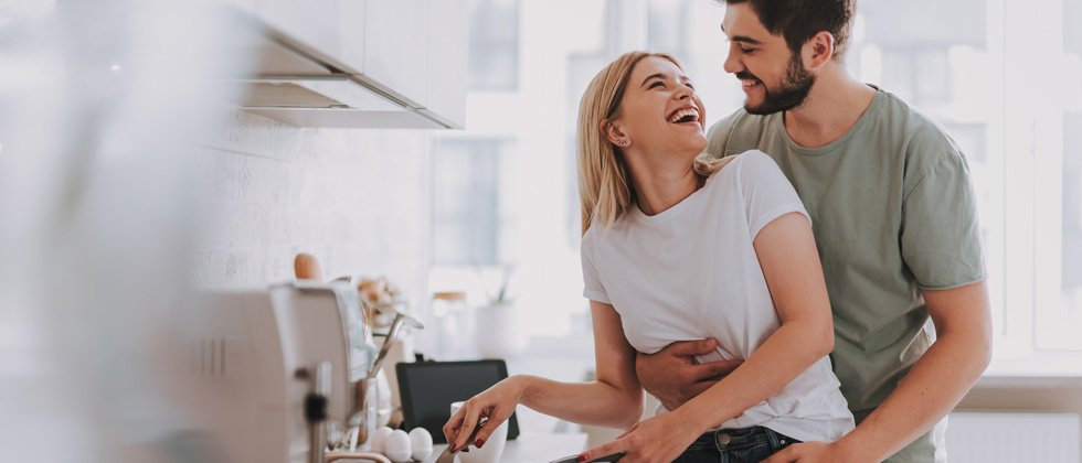 Couple in the kitchen cooking and laughing together