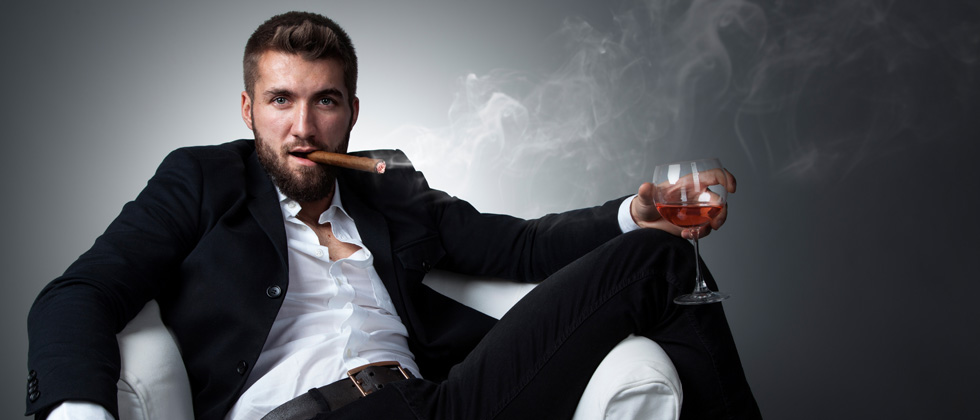 Attractive man lounged on a chair smoking a cigar and drinking wine