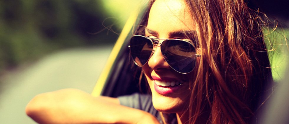 A woman in a car with sunglasses smiling while her head is out the window