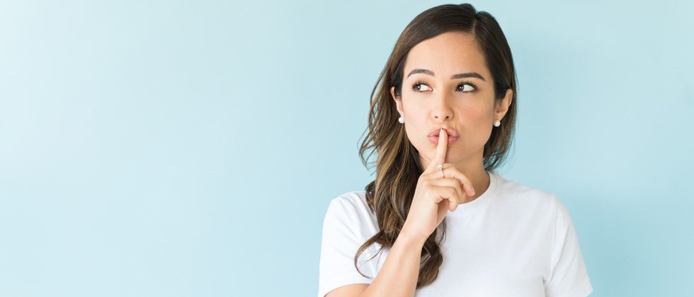 Young woman with her finger over her lips saying shh