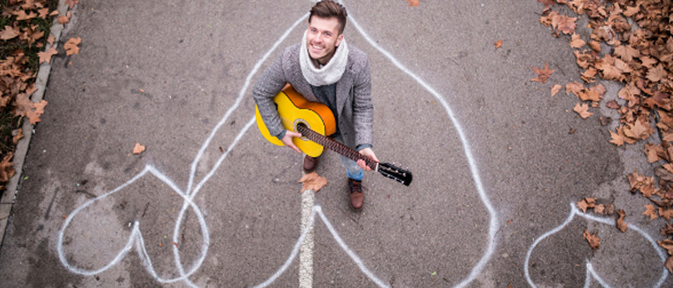Guy standing in a chalk drawn heart playing the guitar
