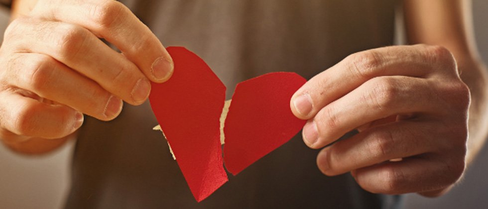 A riped paper heart that's being mended with tape