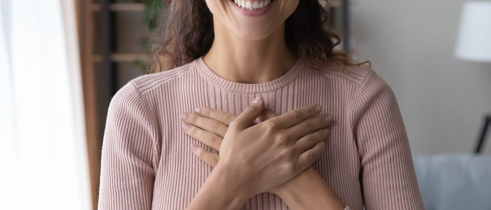 A woman standing with her hands crossing her heart