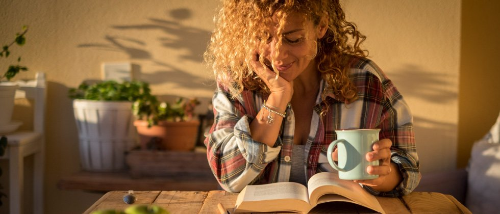 Woman sipping coffee and reading a book in the morning