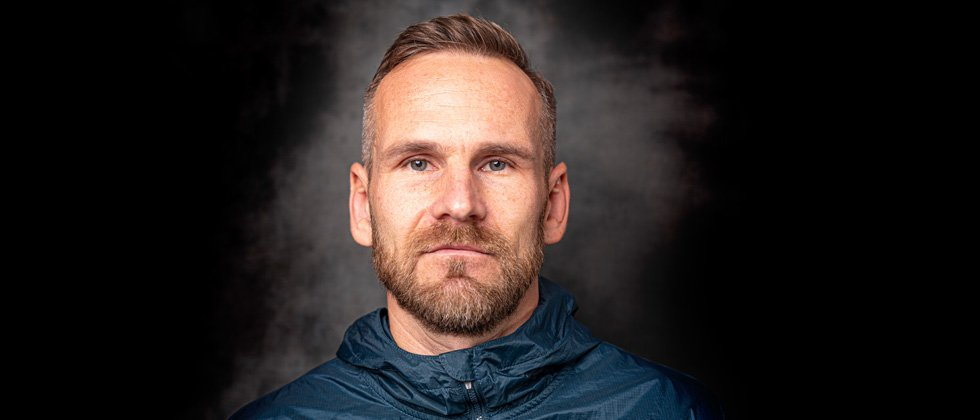 Bearded man looking directly into the camera with intense blue eyes