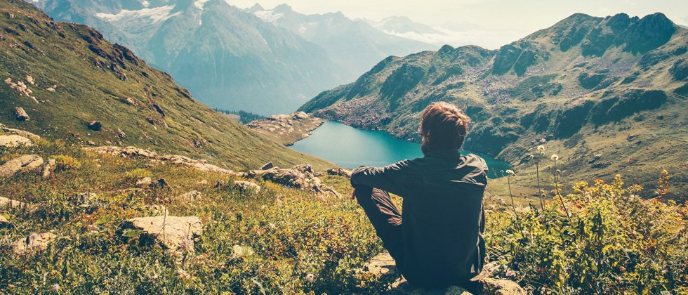 A guy sitting on a rock looking into a mountain valley with a lake at the base
