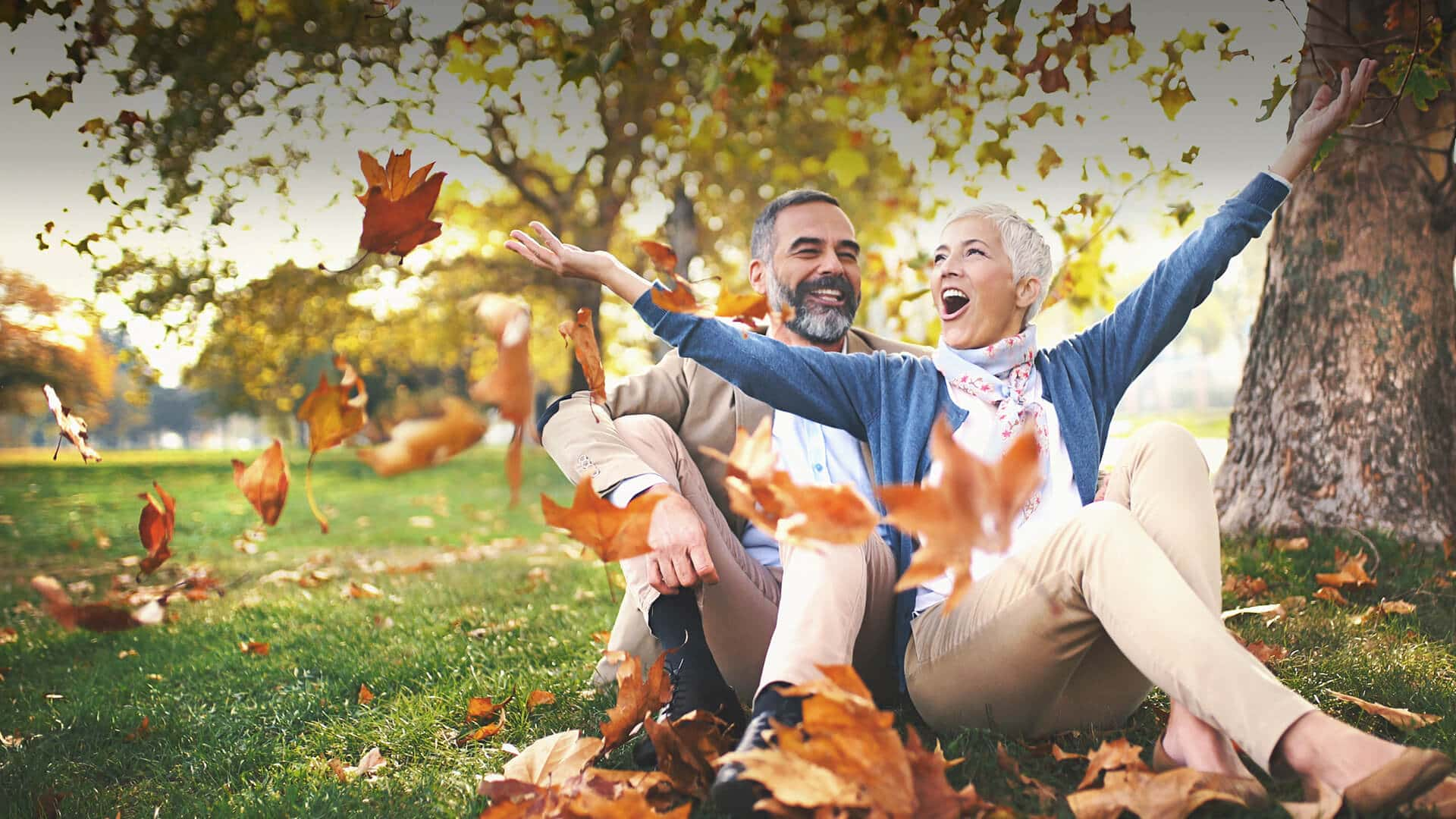 Dating over 50 symbolized by a happy man and woman sitting in the meadow of a park