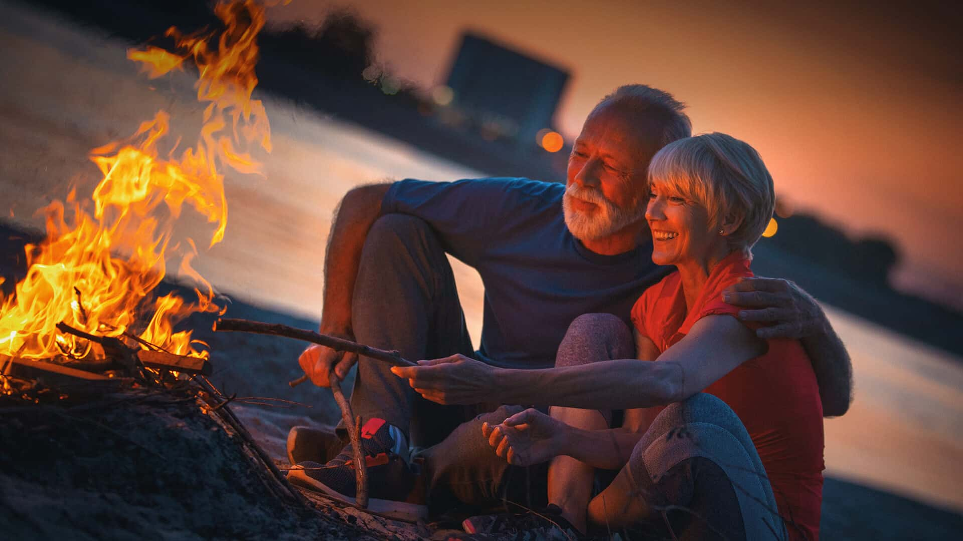 60s dating symbolized by a happy couple sitting in front of a campfire