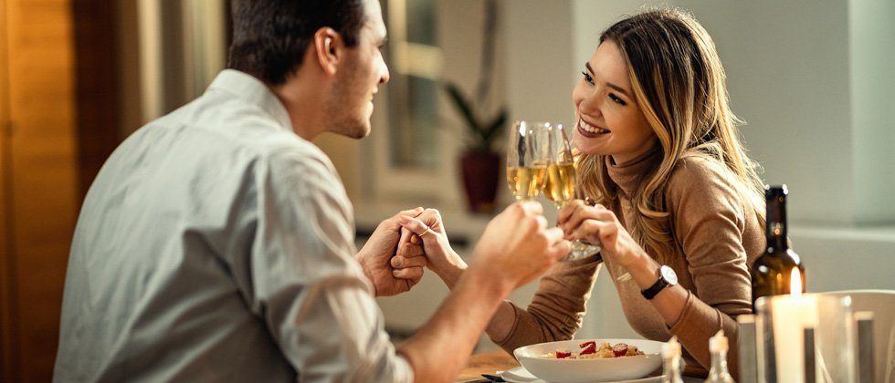 Couple on a dinner date drinking wine and holding hands