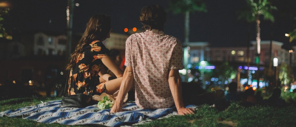 A young couple sitting on a picnic blanket in the park at night