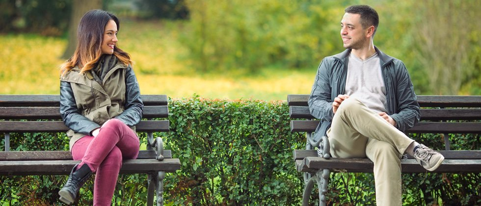 A man & woman sitting on separate park benches chatting