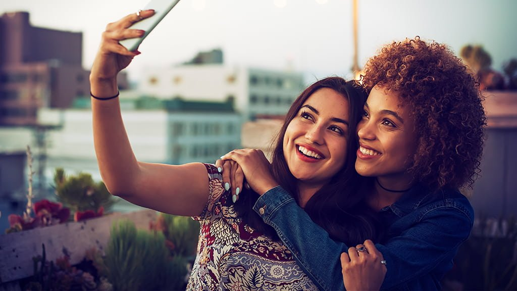 Lesbian dating illustrated by two women who embrace each other and take a selfie