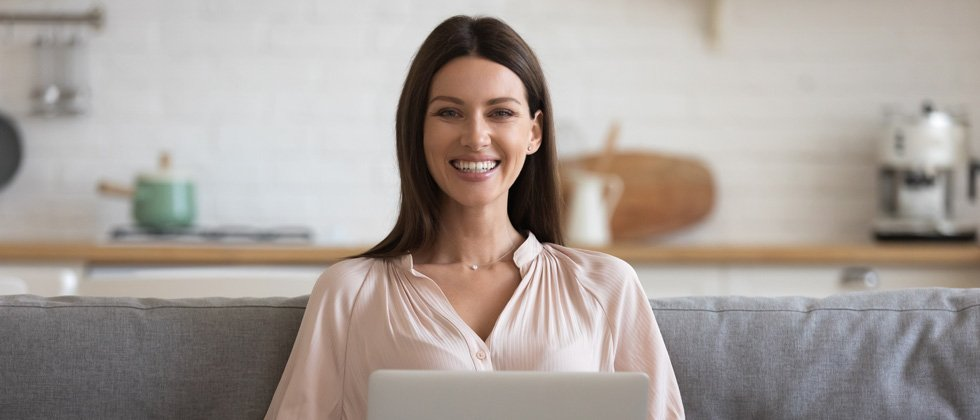 A woman smiling at the camera with her laptop on her lap
