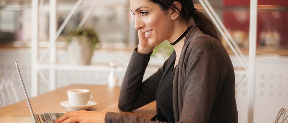 A woman sitting at a cafe working on her laptop