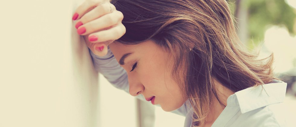 Frustrated woman leaning against a wall with her eyes closed