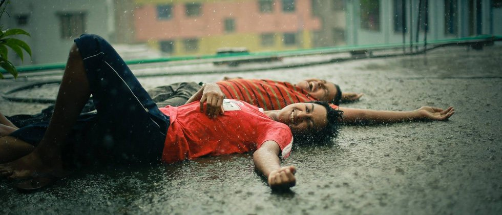 A couple laying on the ground in the rain laughing
