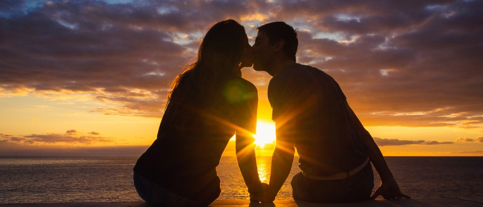 Couple kissing at sunset on the beach with the sun between them