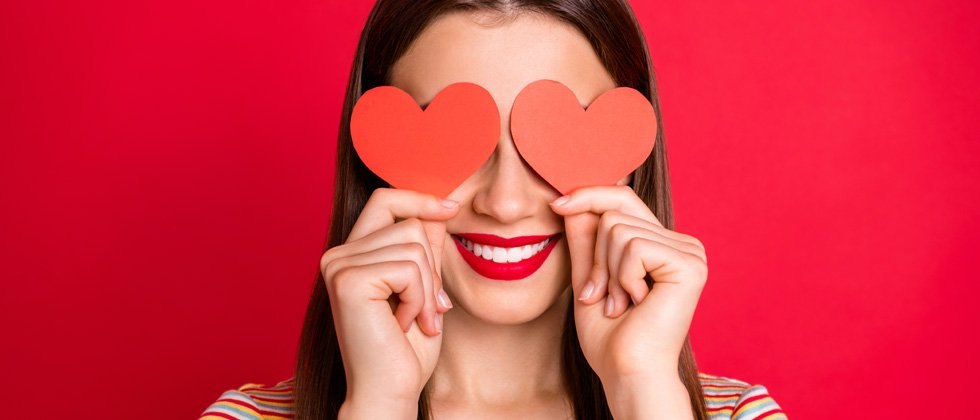 Young girl smiling holding hearts over her eyes