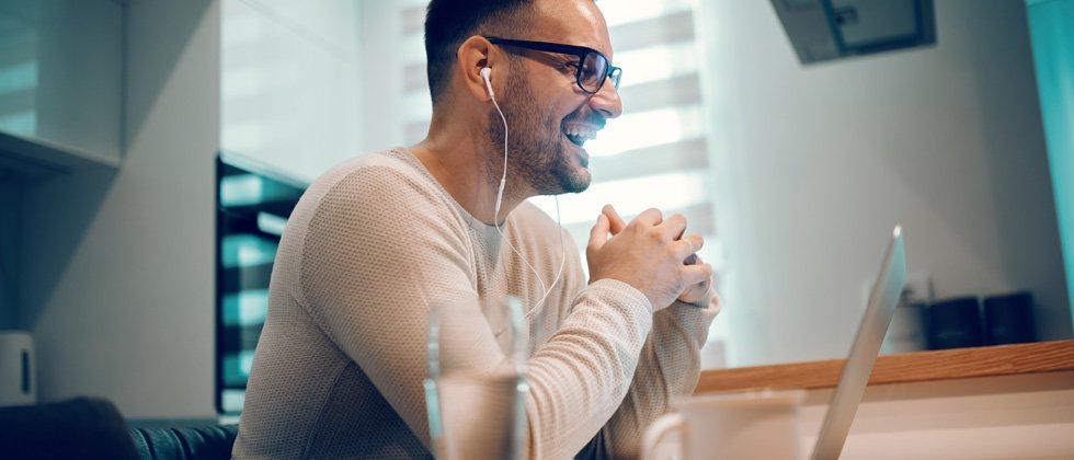 Man on his computer with headphones laughing