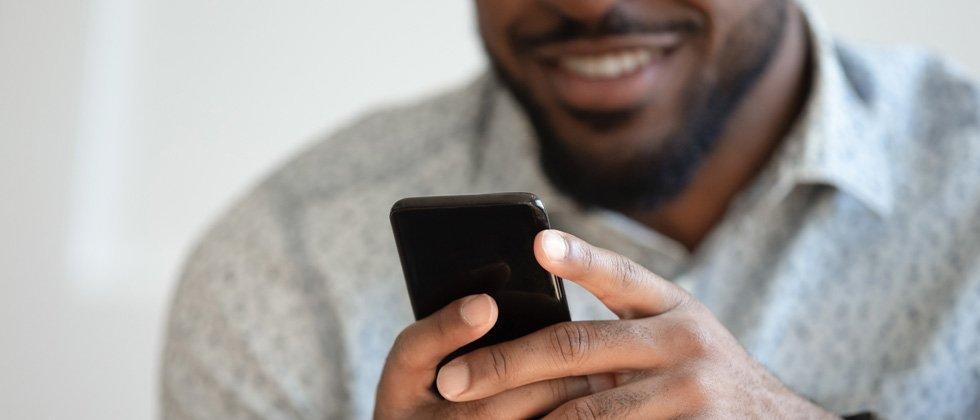 Guy texting on his cell phone and smiling