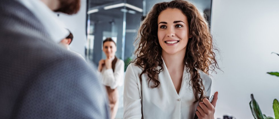 Young professional woman smiling while having a conversation