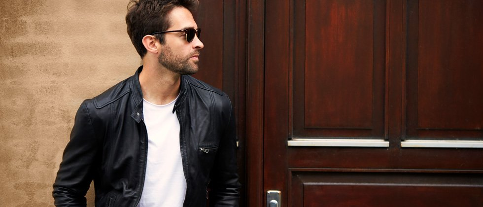 A guy in a leather jacket and sunglasses looking away as he walks